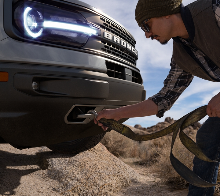 A person attaching a harness to the front trailer tow hooks on a 2021 Ford Bronco Sport