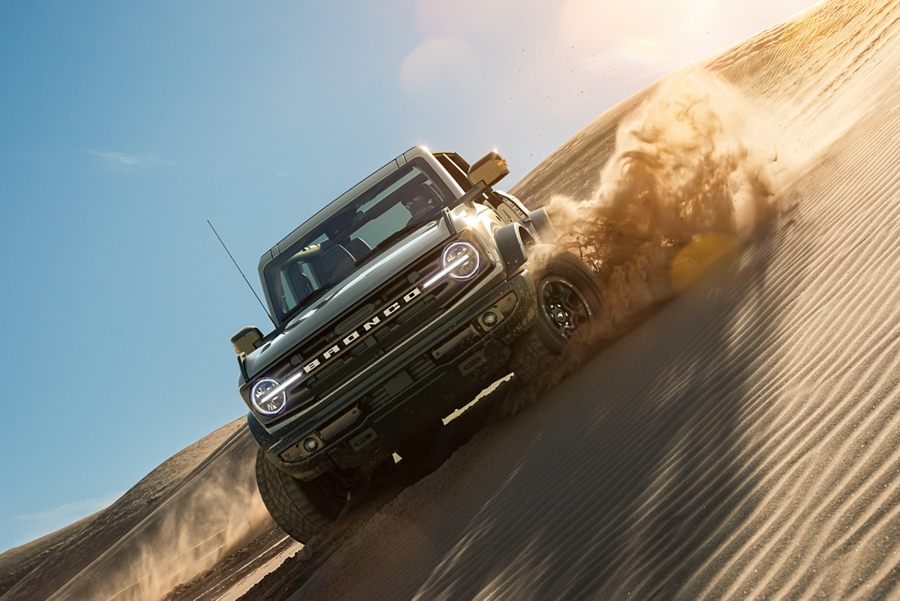 A 2021 Ford Bronco being driving through sand dunes