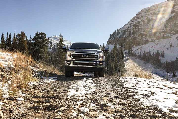 2020 Ford Super Duty LARIAT shown in Iconic Silver driving up snowy mountains