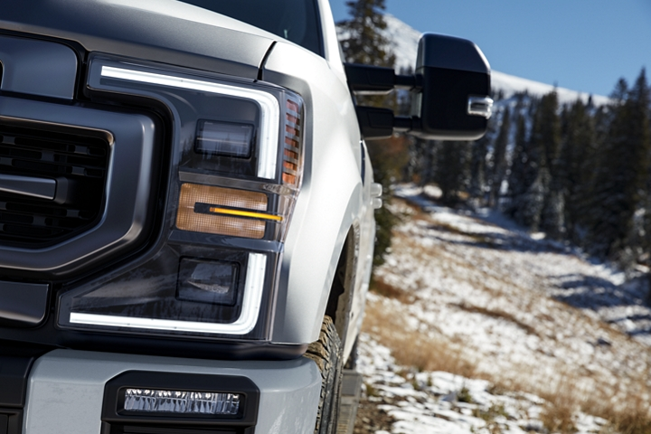 Close up on 2020 Ford Super Duty in Star White Front Headlamps and L E D Fog Lamps with snowy hill in background