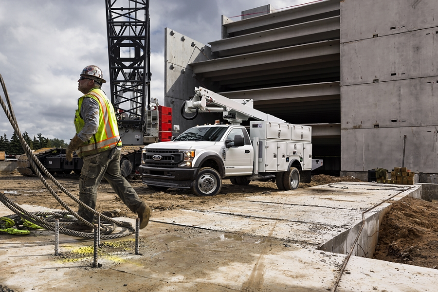 Construction worker walking near 2020 Super Duty Chassis Cab with upfit at worksite