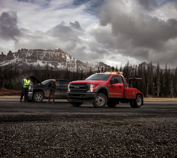 2020 Ford Super Duty F 450 X L Chassis Cab in Race Red near additional truck on road with mountains and trees in background