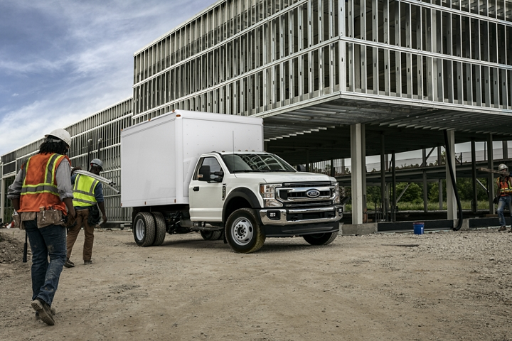 Construction workers carrying materials towards 2020 Ford Super Duty X L T F 600 Chassis Cab shown in Oxford White with box truck upfit at worksite