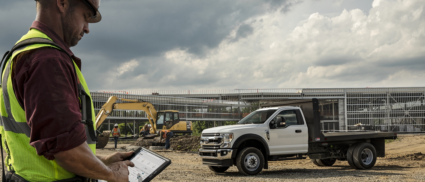 Worker using tablet near 2020 Ford Super Duty Chassis Cab with upfit parked on dirt at construction site
