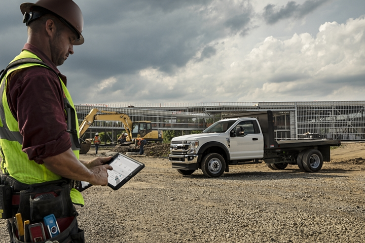 Tablet in front of Man using 2020 Ford Super Duty X L T F 600 Chassis Cab shown in Oxford White with flat bed upfit at construction site