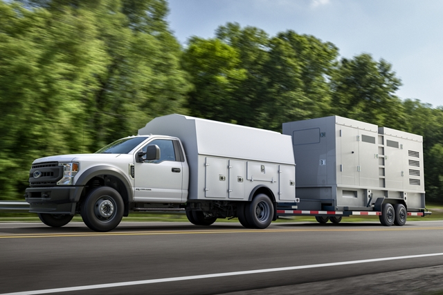 2020 Ford Super Duty Chassis Cab with utility box upfit and trailer in tow being driven on road near trees
