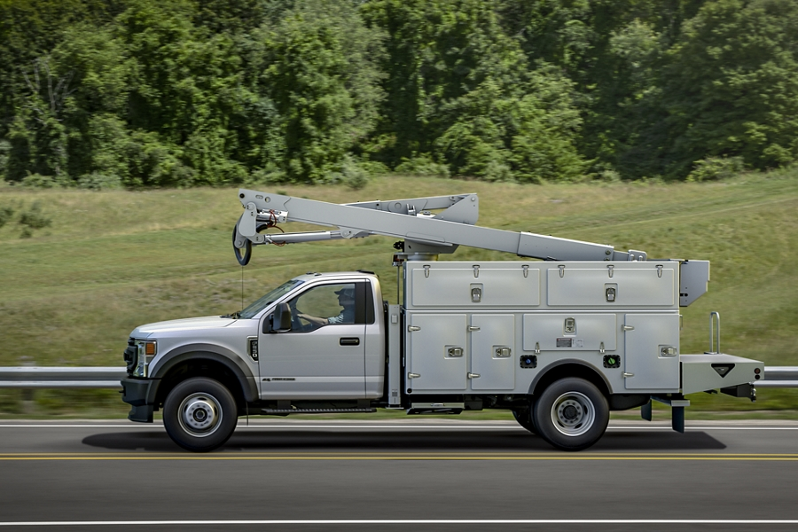 2020 Ford Super Duty Chassis Cab with flatbed being driven on road side view