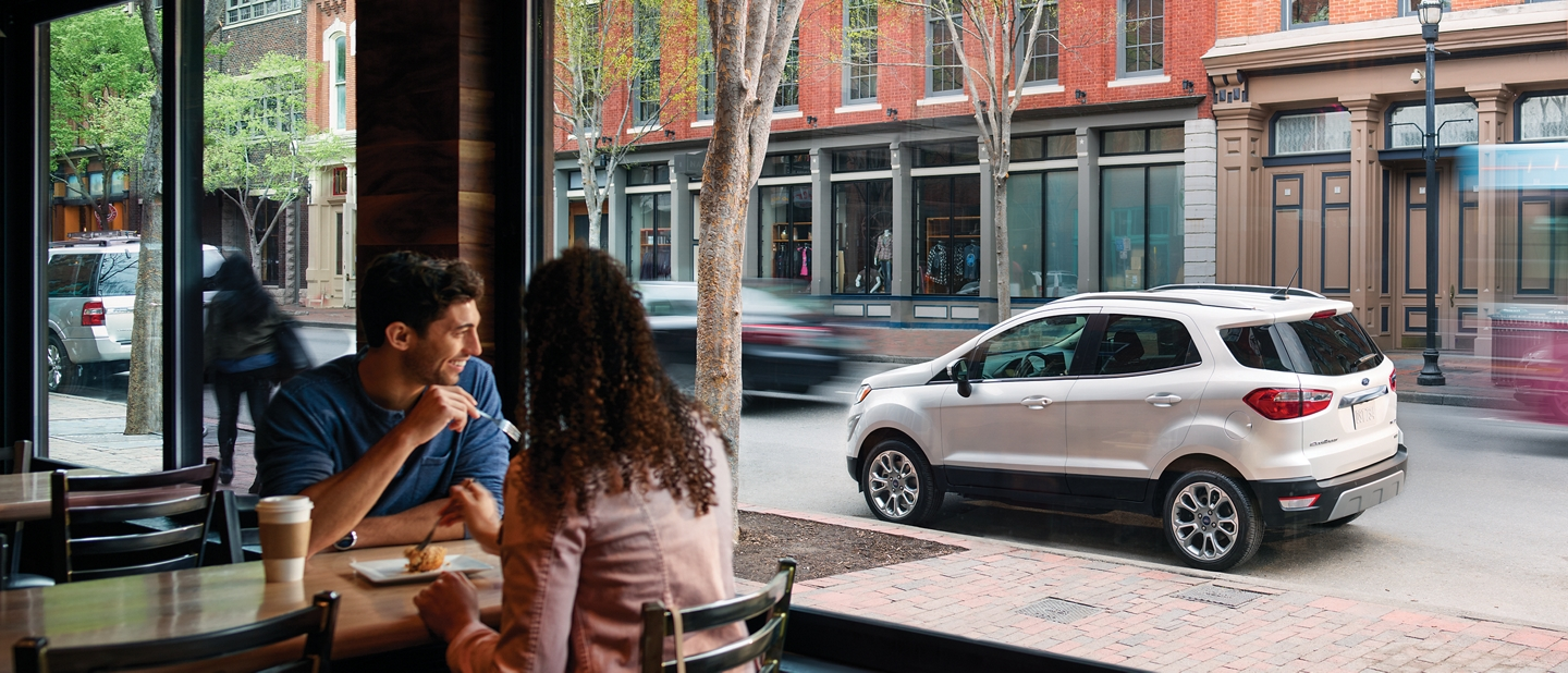 A couple looks at a 2019 EcoSport Titanium in Diamond White through a restaurant window