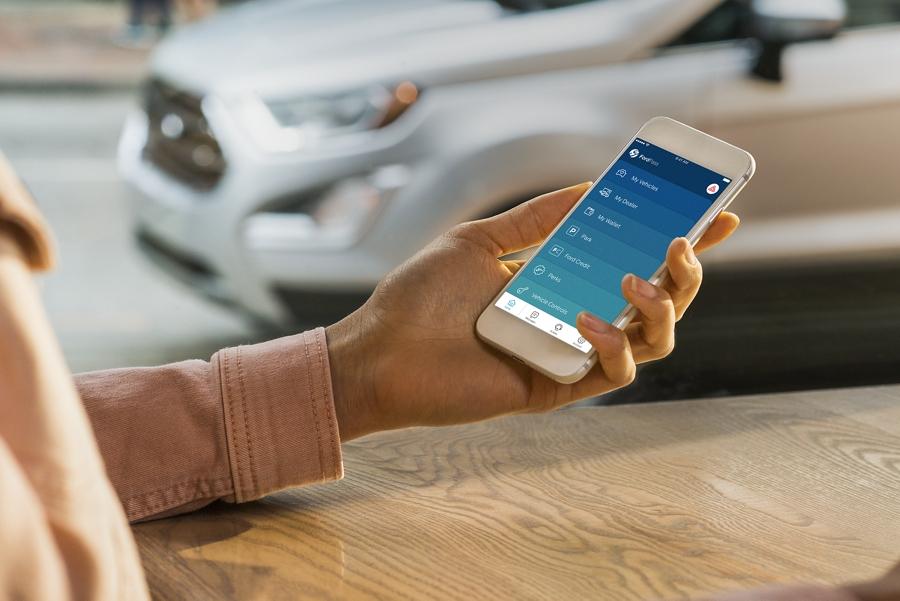 Una mujer accede a FordPass en su teléfono