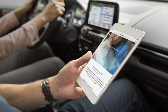A passenger in the 2019 EcoSport uses available FordPass Connect with 4 G L T E WiFi Hotspot with his electronic notepad