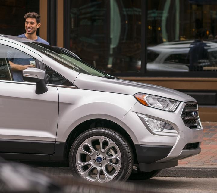 Pareja subiéndose a una Ford EcoSport Titanium 2019 en Moondust Silver estacionada