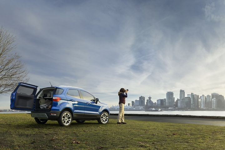 Woman taking pictures of nearby city next to the 2019 Ford EcoSport Titanium in Lightning Blue with its stylish rear swing gate open