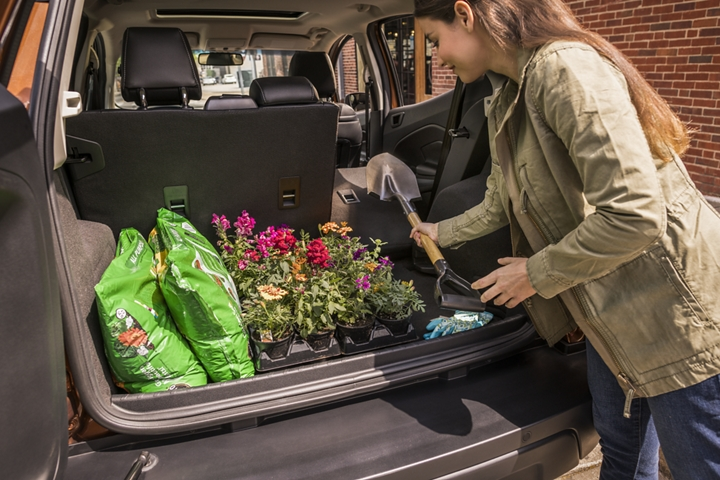 Woman loading gardening supplies into the extra cargo room provided by the 2019 EcoSports fold flat second row seating