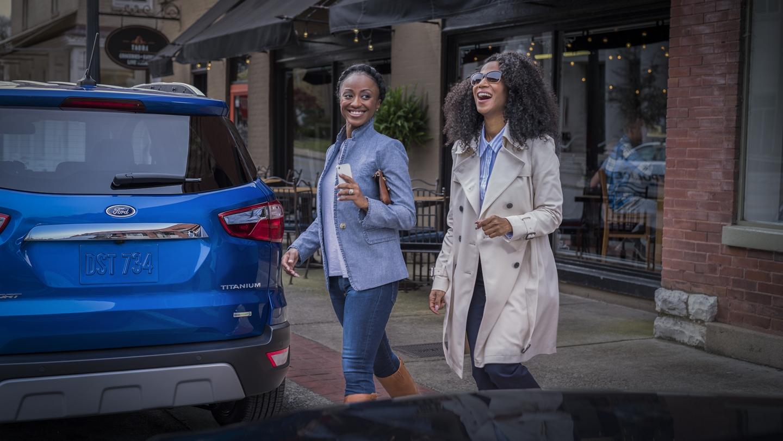 Mujeres caminando para subir a una EcoSport 2019 después de pasar un día divertido