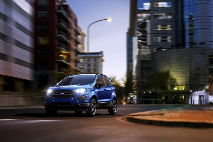 2019 EcoSport S E S in Lightning Blue using its halogen headlamps to light up a city street
