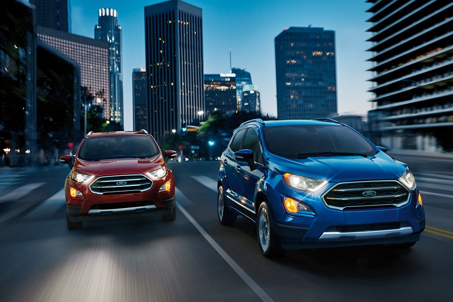 The 2019 EcoSport Titanium in Lightning Blue on a city street with another EcoSport in Ruby Red behind on its right
