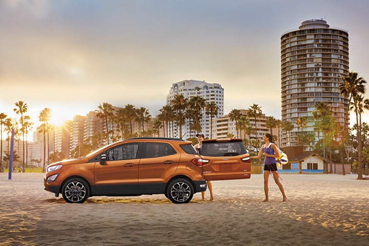 Two women loading sports gear into a 2020 Ford EcoSport S E S in Canyon Ridge with rear swing gate open