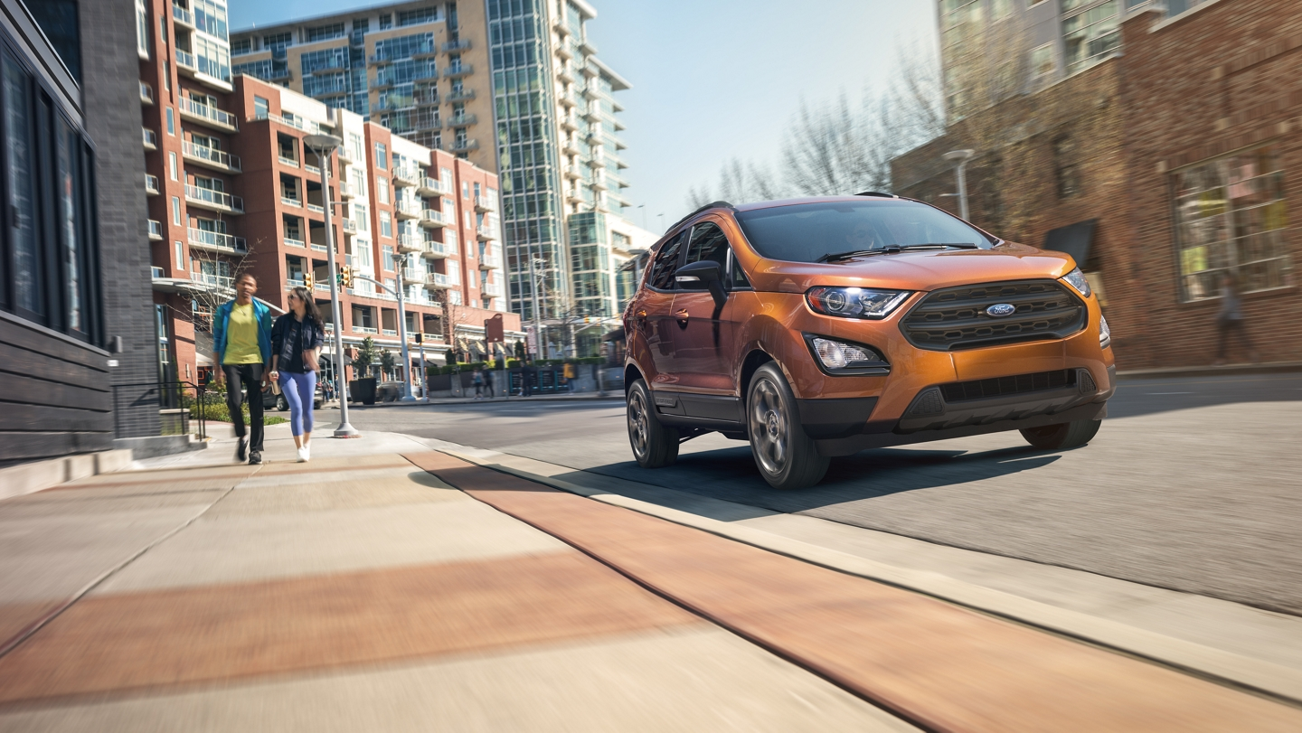 A 2020 Ford EcoSport in Canyon Ridge being driven down a city street