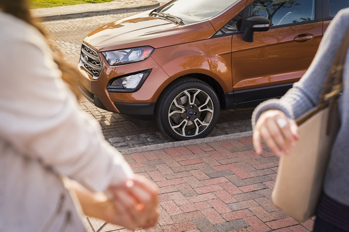 Two people standing near a 2020 Ford EcoSport with 16 inch Low Gloss Magnetic Painted Machined Face Aluminum wheels