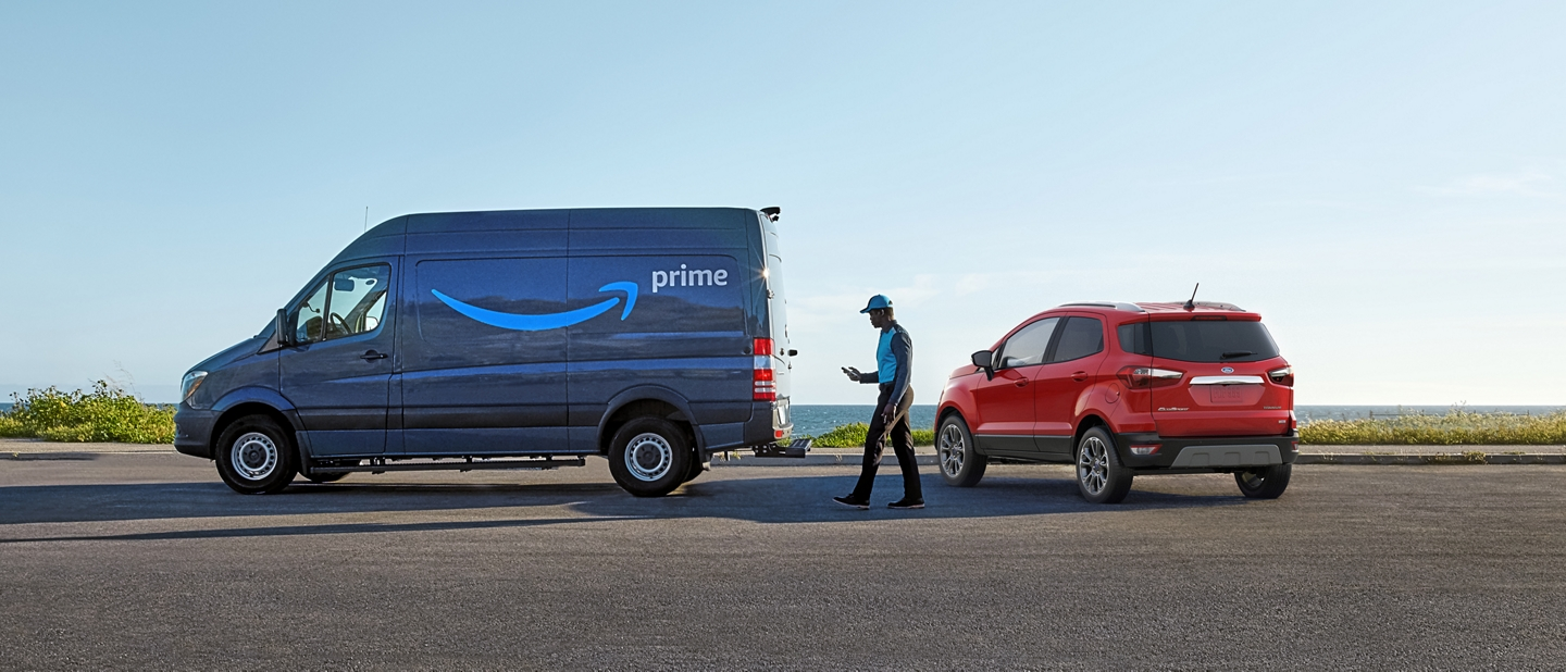An amazon delivery driver walking away from a 2020 Ford EcoSport towards his Prime delivery truck