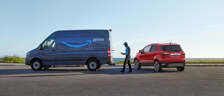 Un conductor de entregas de Amazon alejándose deunaFordEcoSport2020 y caminando hacia una camioneta de entregasPrime