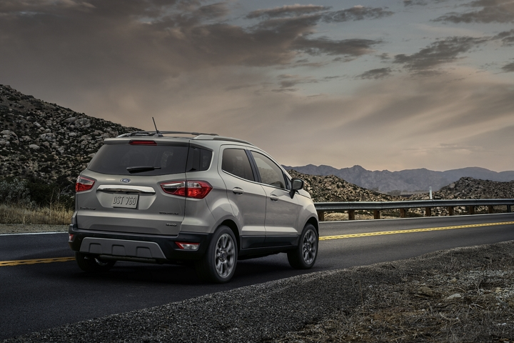 2020 Ford EcoSport Titanium in Moondust Silver being driven on curved mountain road in the evening