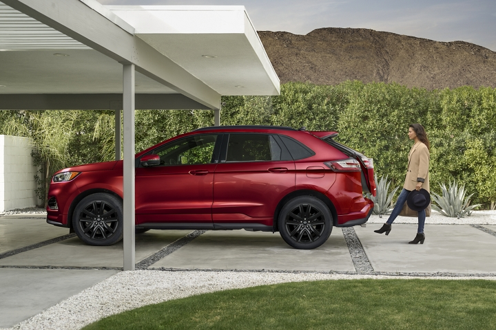 Woman using hands free foot activated liftgate on rear of 2020 Ford Edge S T Line in Rapid Red