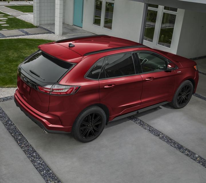 Una Ford Edge S T Line 2020 en Rapid Red estacionada en una entrada de una casa moderna