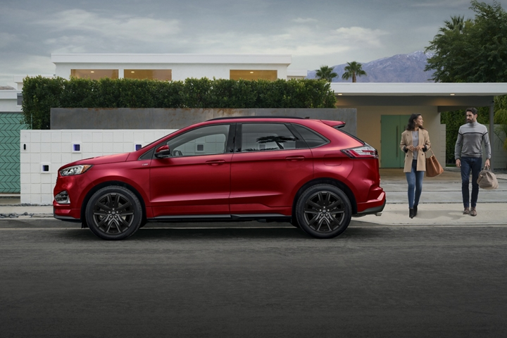 Man and woman walking near 2020 Ford Edge S T Line in Rapid Red parked in front of large home