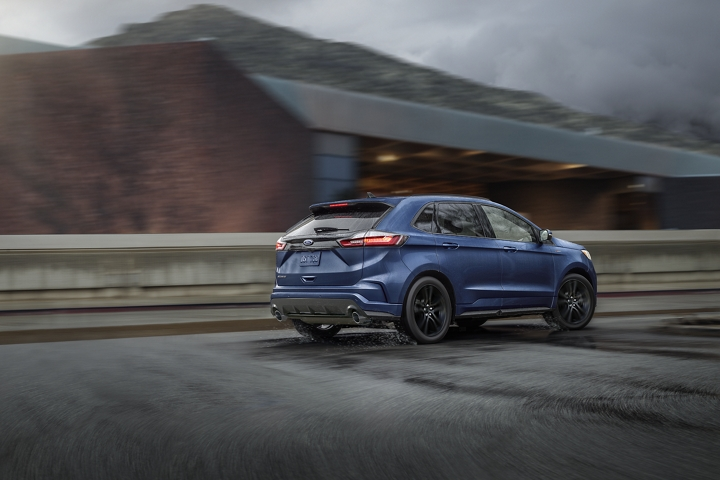 Rear view of 2020 Ford Edge S T Line in Atlas Blue being driven on road
