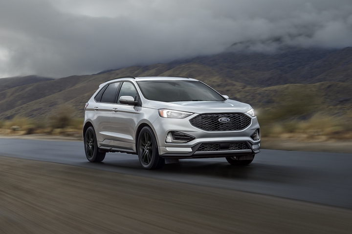 2020 Ford Edge S T Line in Iconic Silver being driven on road near mountains