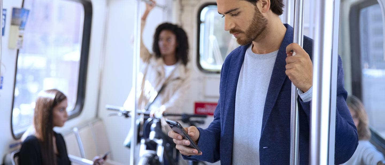 Hombre en un vagón de tren público mirando susmartphone