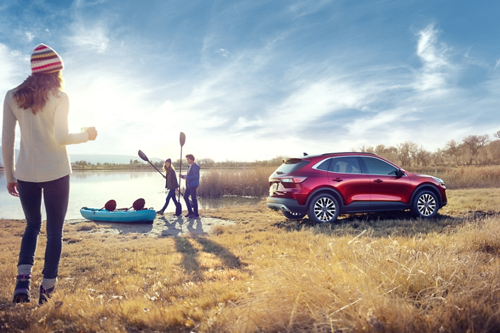 2020 Ford Escape Titanium gas in Rapid Red Metallic Tinted Clearcoat with a young group boating by a lake