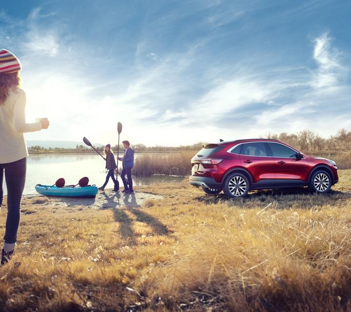 Ford Escape Titanium 2020 de gasolina en Rapid Red junto a un grupo de jóvenes que van a subir a un bote en un lago