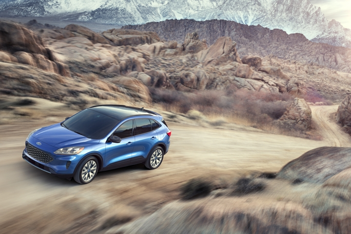 2020 Ford Escape S E Sport Hybrid in Velocity Blue shown driving a mountain road