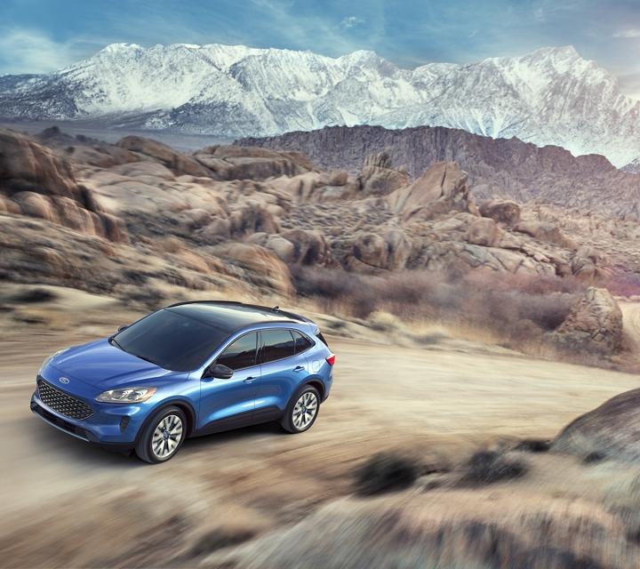 Imagen de la Ford Escape S E Sport Hybrid 2020 en Velocity Blue por una carretera montañosa