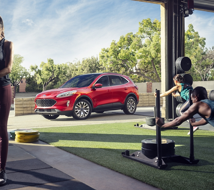 2020 Ford Escape Titanium in Rapid Red parked outside a busy fitness center