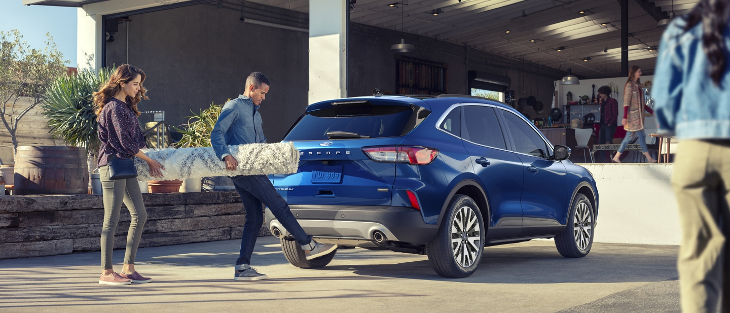 A couple uses the hands free foot activated liftgate to load their 2020 Ford Escape Titanium Hybrid
