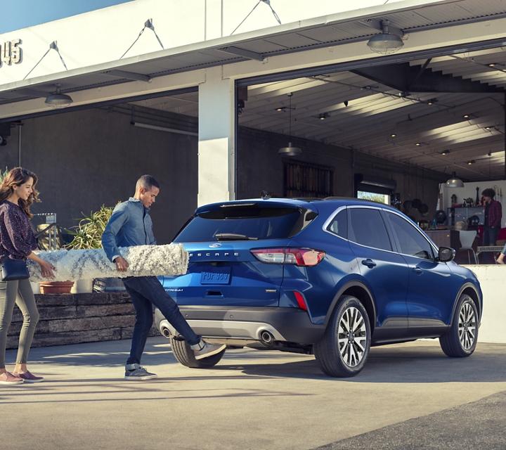Una joven pareja usa la puerta levadiza trasera manos libres que se activa con el pie para cargar su Ford Escape Titanium Hybrid 2020