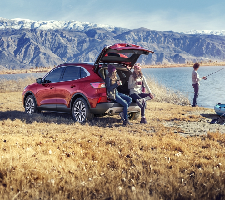 2020 Ford Escape Titanium gas model in Rapid Red Metallic Tinted Clearcoat with a young family by a lake