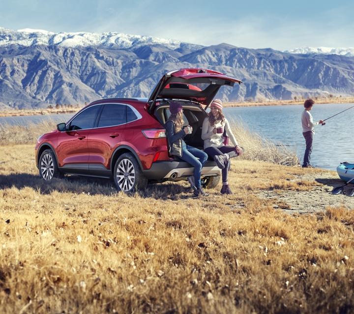 Modelo Ford Escape Titanium 2020 de gasolina en Rapid Red Metallic Tinted Clearcoat con una familia joven junto al lago