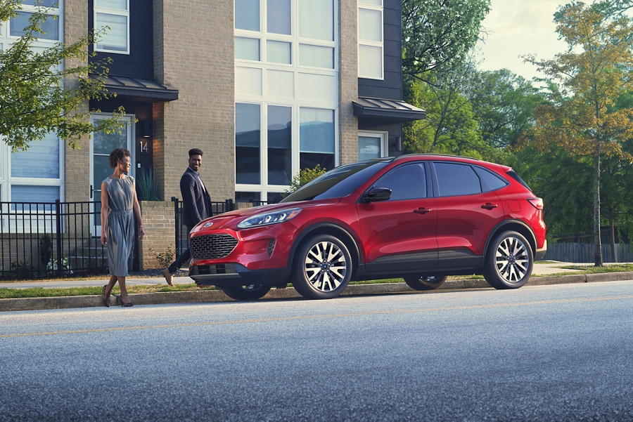 A couple walking toward a parked 2020 Ford Escape S E Sport Hybrid in Rapid Red Metallic Tinted Clearcoat
