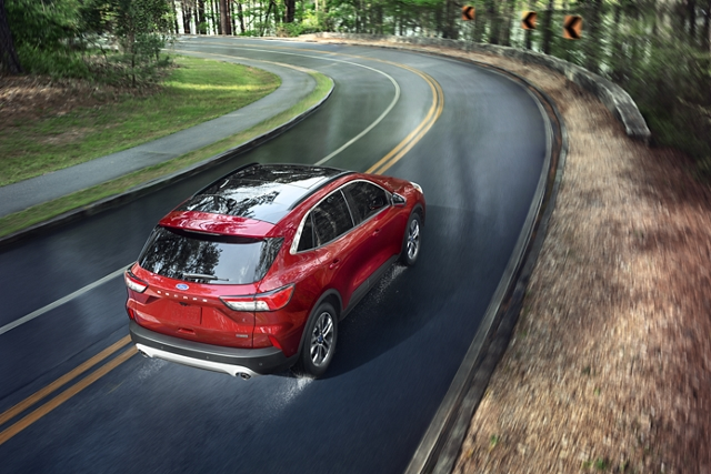2020 Ford Escape in Rapid Red Metallic Tinted Clearcoat on the road heading into a curve