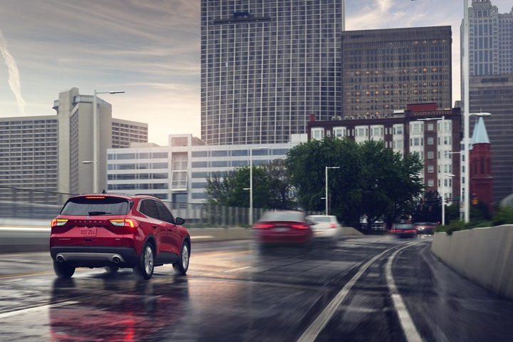 Rear view of 2020 Ford Escape Titanium being driven on a road in the rain