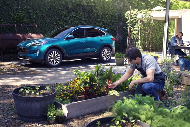 Dark Persian Green 2020 Ford Escape Titanium parked where people are gardening
