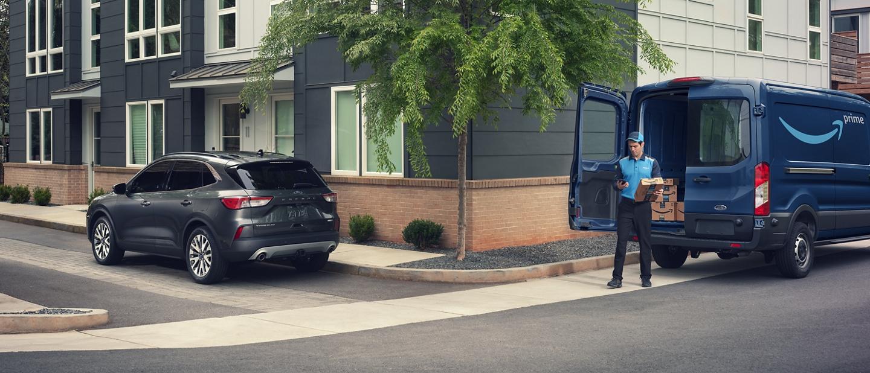 Empleado de Amazon entregando un paquete a una Ford Escape 2020 estacionada en un área residencial