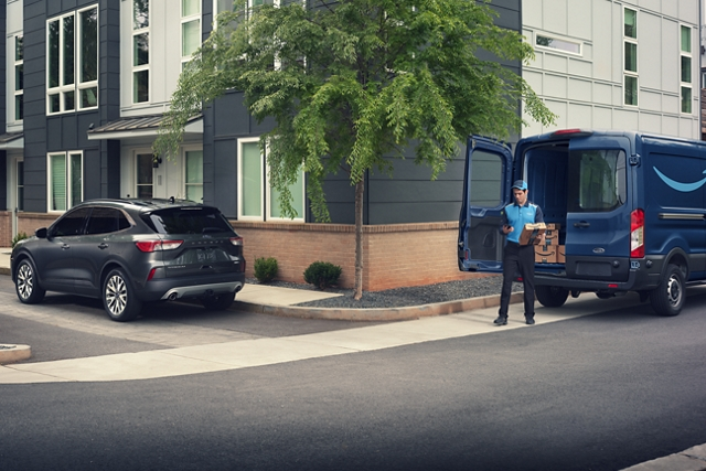 Amazon courier delivering a package to a 2020 Ford Escape parked in a residential area