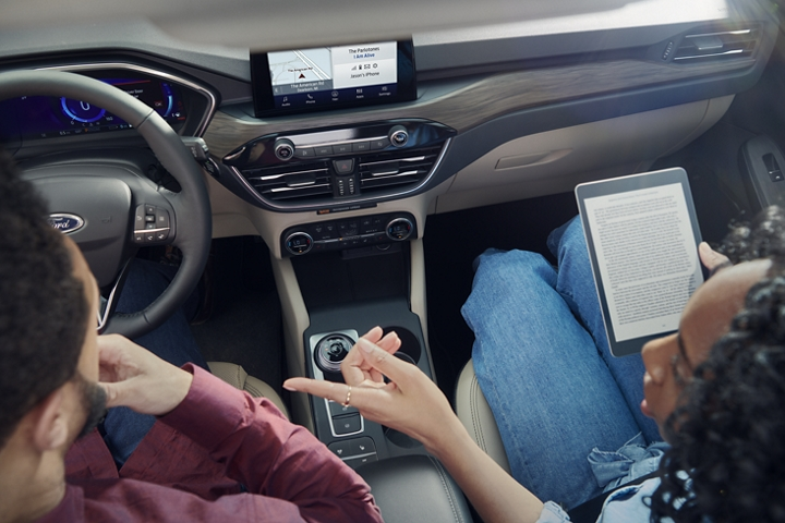 Interior view of a driver behind the wheel and a passenger holding a computer tablet