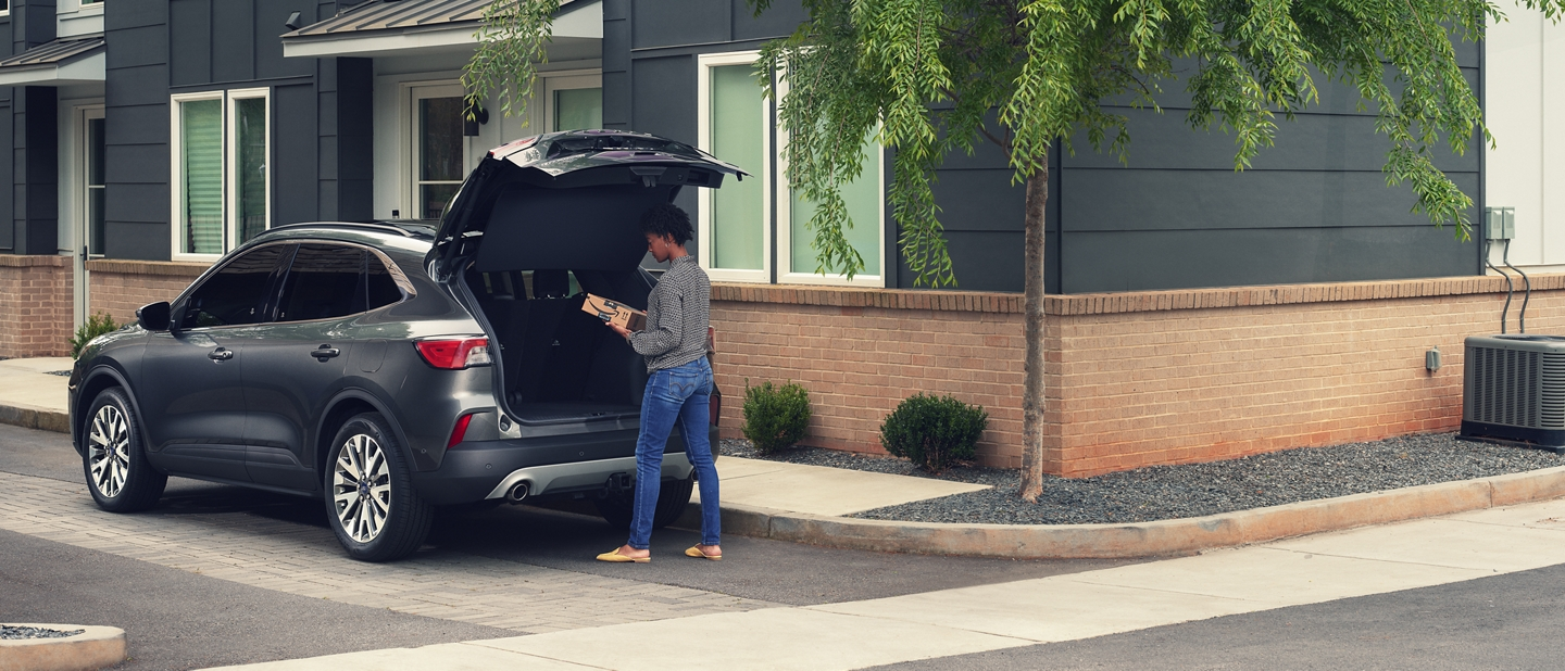 Woman retrieving an Amazon package from the cargo area of a 2020 Ford Escape
