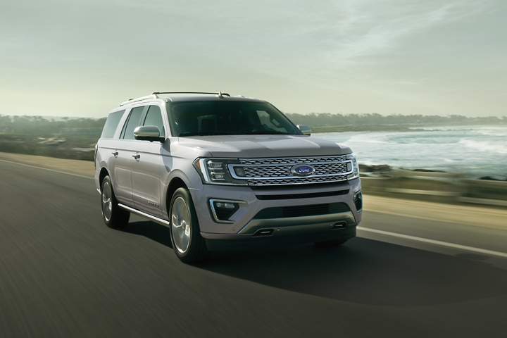 2020 Ford Expedition Platinum with distinctive grille being driven along an ocean road